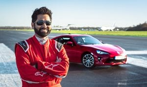 Dr Amit Patel @BlindDad_Uk stands in front of a red Toyota GT86 at a race track in Surrey.