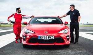 Dr Amit Patel and instructor Mark Watkins, stand on the race track, either side of the Toyota GT86