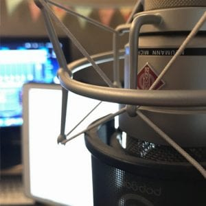 A Neumann TLM103 microphone in Natalie Cooper's studio. In the background an iPad screen is used for reading scripts, and a computer monitor shows a mixing desk.